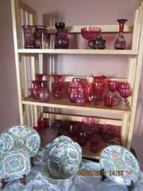 Cranberry glass on the shelves is a part of all that is in the sale.  The purple glass oil lamp on the top shelf is unique. The Chinese export dishes and bowl on the table is all in good condition. Ruby stain is also seen.