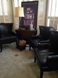 Three of four brownish/black leather chairs