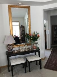 Lg gold framed mirror, 3 feet wide over an Ethan Allen table with 2 black lacquer stools with upholstered seats