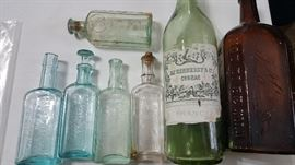 Very old embossed medicine bottles and Hennessy bottle.