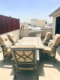 Stone Patio table, 6 chairs w/ cushions, & wrought iron umbrella stand