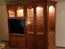 solid wood entertainment center with curio cabinets on each end,  Lighted glass