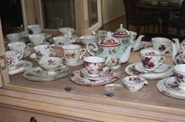 Large collection of tea cups and tea pots.