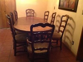 Century dining table and 8 chairs. Table has two leaves and can be reduced to a round table.