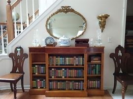 "Vintage English mahogany bookcase, (measures 5' 1"" L x 12 1/2"" D x 40"" T) with floral inlay, vintage gilt wood oval mirror, collection of leather bound books, flanked by a pair of antique English mahogany slipper chairs.                                                                                         The wall sconce is an antique French gilt carved wood wonder!"