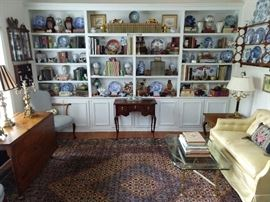 "Library FULL of collectibles, including blue/white porcelain, leather bound older books, Asian plates and vases, cast iron toys, artwork, etc.,  all atop a vintage Persian Bijar rug, hand woven, 100% wool face, measures 8' 5 ""x 11' 10""."