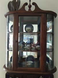 Close up of the vintage mahogany mirrored,  wall-mounted curio cabinet, with hand painted English porcelain tea set.