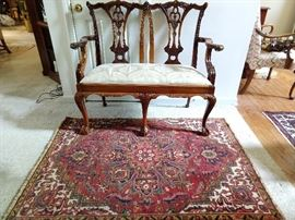 "Mahogany Chippendale style settee, on a vintage Persian Heriz, measuring 3' 10"" x 5'."