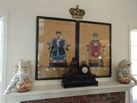 Pair of nicely executed Chinese ancestral portraits, on silk, flanked by a wonderful pair of porcelain foo dogs. French marble mantle clock in the foreground.