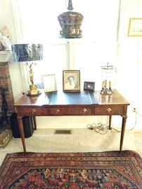 Wonderful Baker 3-drawer mahogany desk, with Asian gilt wood table lamp, vintage hanging brass swag lamp, French 3-light bouillotte lamp, all atop a vintage Persian Malayer hand woven rug.