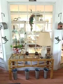 The screened porch has a fun collection of goodies to offer, like this bamboo console table with glass top, vintage French galvanized tin flower buckets, trailer trash galvanized tin birdhouse, vintage galvanized tin GA license plate birdhouse, pair of wall-crawling cast iron geckos - don't forget a vintage plaster Polly - she wants a cracker!