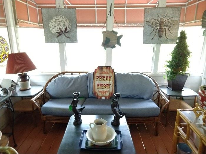 Vintage bamboo sofa, flanked by a pair of desirable Haywood Wakefield bamboo end tables and matching coffee table, pair of cast iron mermaid candleholders, embossed galvanized tin cotton boll and honeybee panels.