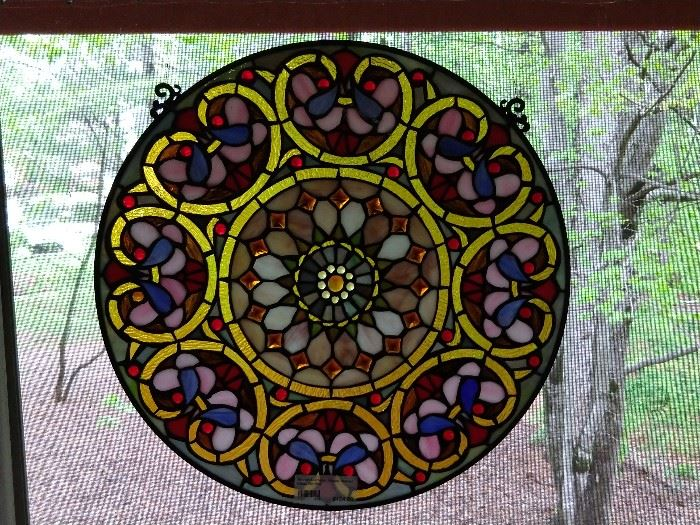 One of a pair of round, stained glass windows.