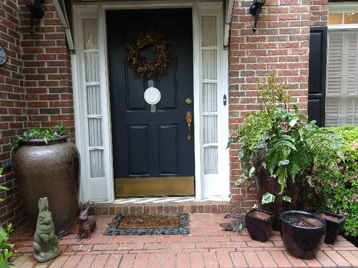 Front door with wreath, holding a bird's nest with four fledgling birds. I hope they'll be gone by the time we open the doors for the sale, but they've been fun to watch from eggs to birds! Pair of 4' tall glazed pottery urns, vintage concrete bunny, with good green patina, a pair of cast iron bunnies, and set of three black glazed terra cotta pots.