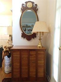 Hand made louvered door pine cabinet, 3-light brass table lamp, Henredon beveled glass mirror.