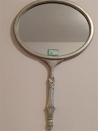 This is a vintage silver leafed wooden wall mirror, that looks like a giant hand-help mirror - cool & groovy!