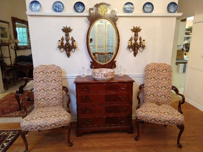 On plate rail: collection of 16 Bing & Grondahl (Copenhagen) plates, pair of flame stitched upholstered wooden armchairs, 4-drawer mahogany chest, Henredon mahogany beveled glass mirror, flanked by a pair of 2-light metal sconces.