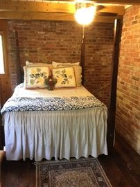 Poster bed, decorator pillows, linen spreads, etc. in an Anthropology style.