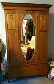Armoire with floral carving on panels and oval mirror