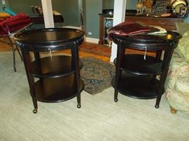 Pair of Walter E. Smithe tiered rolling round tables with pull-out shelf.