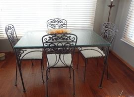 IRON SET WITH CARVED DETAILS AND FLORAL CUSHIONS - 2 SIDE CHAIRS - GLASS END TABLE - 2 SEAT SOFA - GLASS COFFEE TABLE - TABLE AND 4 CHAIRS