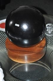 Large round heavy black Chen Yang ceramic sphere shown on a cherry disc