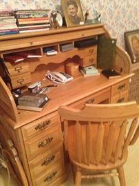 Roll top desk and chair in light wood; desk phone