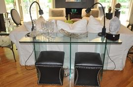 "Heavy glass sofa table (60""w x 30""h x 18""d) shown with a pair of 18"" square black leather storage stools with nailhead detail"