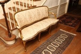 French Regency smaller sofa, gold leaf decoration.  Shown on antique Bokhara rug.