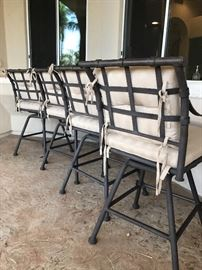 (Backside photograph) 4 Absolutely beautiful solid wrought iron (NOT cast aluminum) high-end barstools with cushions.  These chairs have been placed underneath their patio and were never in direct sunlight.