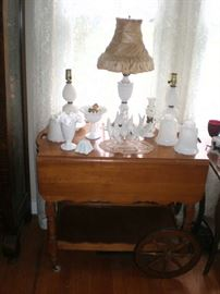 Maple tea cat with drop leaves and lotsof milk glass, inclding a pair of dresser lamps and a lamp with silk shade.