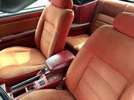 Front seat  of the Mustang, red interior. The yellow is the sunshining in, the seats are in very good condition.
