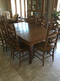 Vintage dining room set with eight wooden ladder back chairs. Table has two leaves.