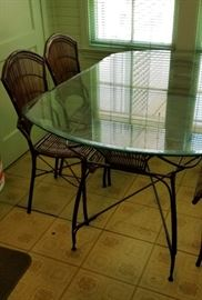cute glass top and iron table and chairs with woven seats and backs