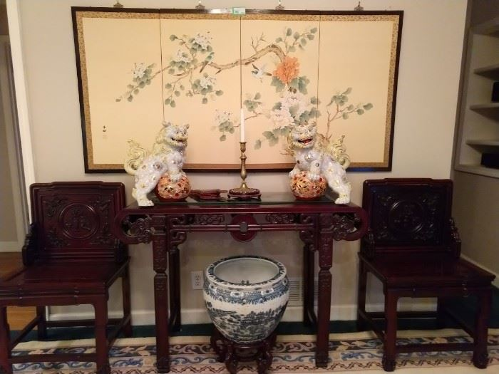 Hand painted 4-panel Chinese silk panel, gorgeous pair of porcelain foo dogs, heavily carved pair of Chinese chairs and matching console table, the rectangular scrolled top over a pierced geometric apron, on squared relief-carved legs joined by stretchers.