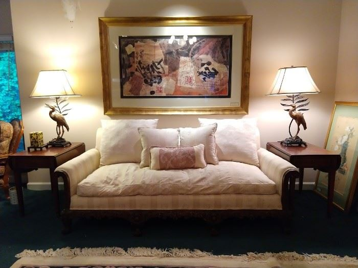 Beautifully carved wooden couch, with down cushion, pair of single drawer drop-leaf mahogany side tables, Pair of crane lamps and well-framed contemporary art.