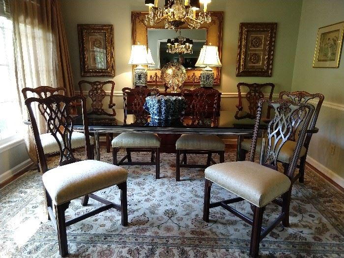 "Dining room, with set of six hand carved mahogany Chippendale chairs (four side, two arm) plus an additional pair of armchairs. The rug is a Persian design Kashan, measuring 8' 6"" x 11' 6"", 1940's Drexel mahogany buffet, pair of blue & white Chinese porcelain lamps, with shades & finials, faux bamboo wall mirror, flanked by a pair of Home Good-ish doodad art things, Imari porcelain charger, St. Louis crystal vase."