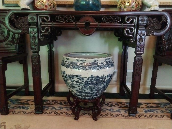 There are several of these Chinese porcelain fish bowls, three of the blue & white ilk. LOVE the carving of the Chinese mahogany console table, complete with glory hole in the middle.
