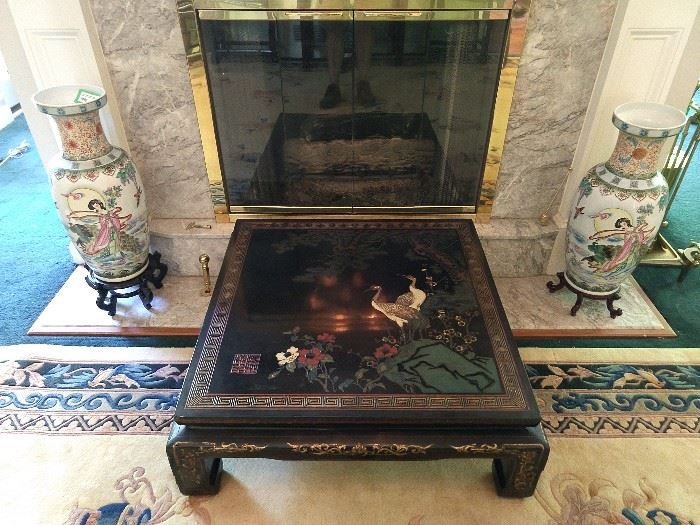 Nice hand carved/painted Asian black lacquer table, with cranes, flanked by a large pair of Asian porcelain vases on wooden stands.