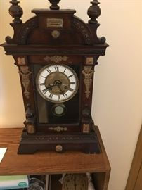Victorian shelf clock with relief figures and gold accents