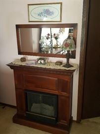 Gas Fireplace/Mantle.  Reverse hand-painted lamp. Wall mirror. Candle snifter.  Floral framed art pieces throughout the home.