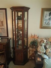 Living Room Curio filled with more trinket treasures.  Lots of wall art.  Dolls. Artificial floral arrangements.