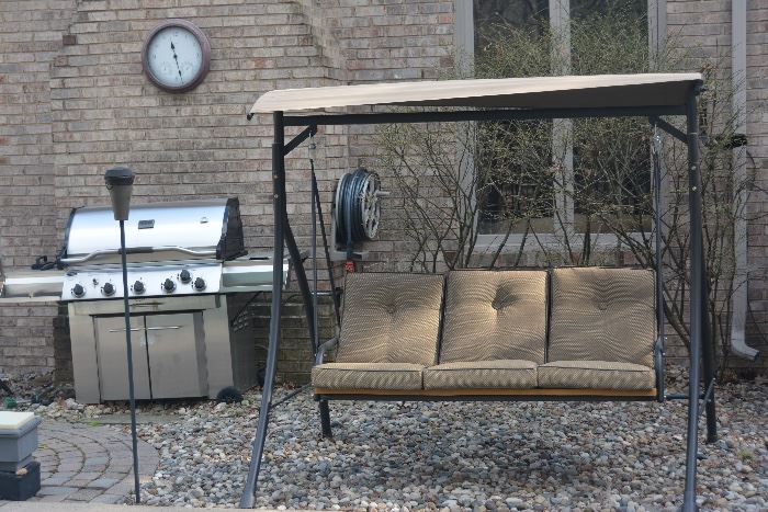 Comfortable outdoor swing in great condition. Also,  stainless steel gas grill and outdoor clock.