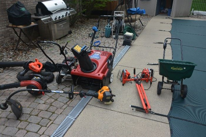 Outdoor equipment. Newer Toro snowblower, Black and Decker electric blower/leaf vacuum, Homelite gas blower, gas weed wacker, gas edger with extra new blades, utility light and lawn fertilizer spreader.