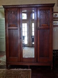 Antique tiger stripe oak wardrobe with a beveled mirror on the center door and hand carving on the two side doors.