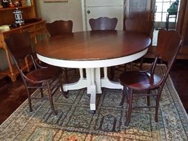 Antique round oak table with a painted base and 5 antique oak chairs.