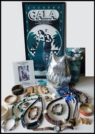 Jewelry including a Unakite bracelet plus other treasures and in the background a gala poster from West Des Moines, Iowa.