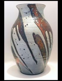Raku pot with brilliant copper glazes. Approximately twelve inches tall. It is much more vivid and shiny than the photo shows.