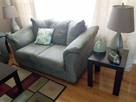 Microsuede loveseat with matching sofa. Black coffee table and two matching end tables