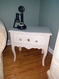 White juvenile nightstand with matching desk, dresser, and tall chest